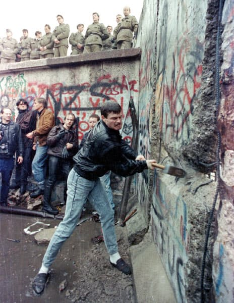 1989年11月、ベルリンの壁をハンマーでたたき壊す男性。頭上に立つ、東ドイツの国境警備隊は傍観していた(ロイター)