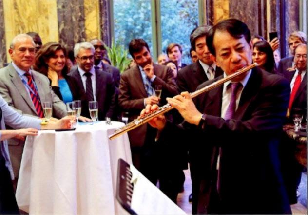 グリアOECD事務総長(左端)の前でフルートを演奏(2015年9月の租税委員会後のレセプションで)