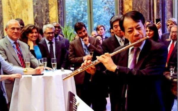 国際会議の場ではしばしば趣味のフルート演奏を披露した(2015年9月、OECDの租税委員会後のレセプションで)