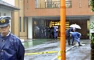 男性が首に刃物で刺されたようなけがを負った事件で、クリニック駐車場を調べる捜査員ら(25日午前9時10分、東京都新宿区市谷山伏町)