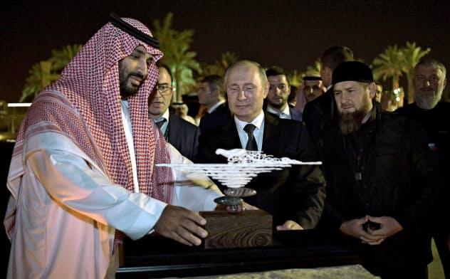 ロシアのプーチン大統領(中央)は中東でのロシアの地政学的な影響力の高まりを経済面での実利につなげたいと考えている(14日、サウジアラビアのムハンマド皇太子=左=に贈り物を披露した)=ロイター