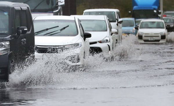 大雨の影響で道路が冠水し、水しぶきを上げて走る車(25日、千葉県君津市)