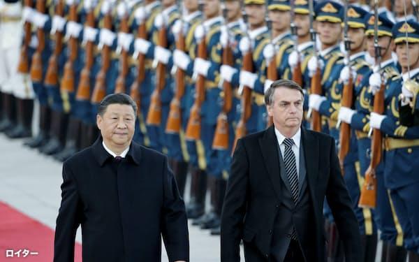 中国の習近平国家主席(左)とブラジルのボルソナロ大統領は北京で会談に臨んだ(25日、北京)=ロイター