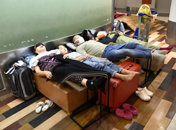 大雨の影響で足止めされ、成田空港で夜を過ごす人たち(26日未明)=共同
