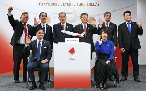 聖火特別輸送機の模型と記念撮影する野村忠宏さん(前列左)と吉田沙保里さん(同右)ら(25日、東京都中央区)