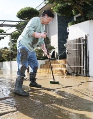 浸水した住宅にたまった泥を流す女性(26日、千葉県茂原市)