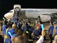 バニラ・エアとして最後の成田到着便の乗客を従業員らがイメージカラーの青と黄色のサイリウムを手に出迎えた(26日、成田空港)