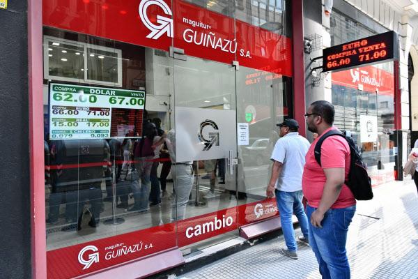 ドル不足により、両替商の店舗から閉め出された人々(25日、ブエノスアイレス)