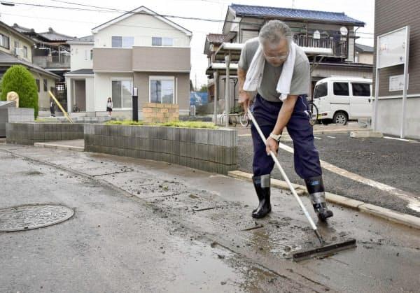 浸水被害のあった千葉県佐倉市で道路の泥を片付ける住民(27日午前9時36分)=共同