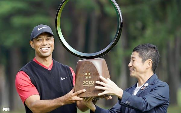 ZOZOチャンピオンシップで優勝を決め、前沢友作氏からトロフィーを受け取るタイガー・ウッズ(28日、千葉県の習志野CC)=共同
