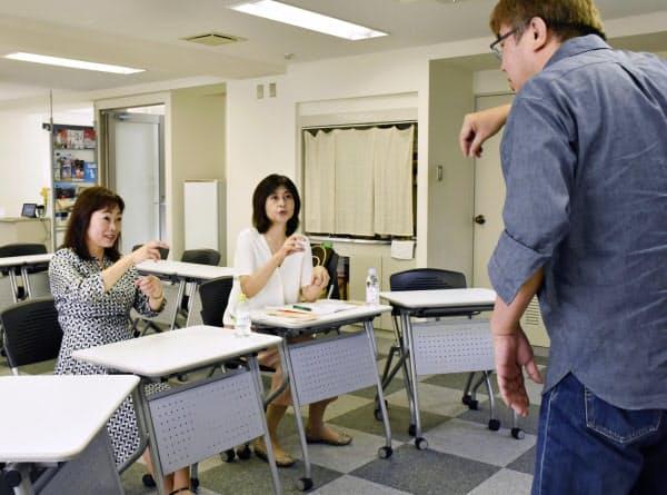 国際手話中級講座で学ぶ青塚昌子さん(左)。右は講師の砂田武志さん(5日、東京都千代田区)=共同