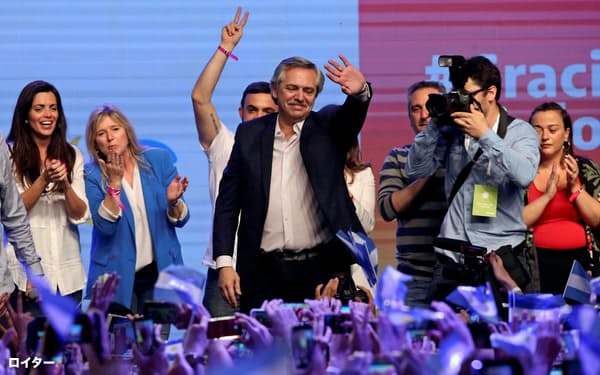 支持者の声援に応えるアルベルト・フェルナンデス元首相(中)(27日、ブエノスアイレス)=ロイター