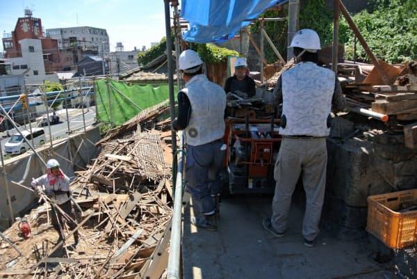 狭い区画のため重機が入らず、手作業で空き家を解体する作業員(広島県尾道市)