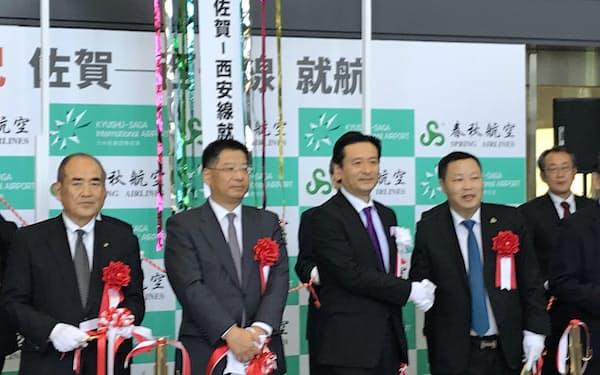記念式典で春秋航空の瀋巍副総裁(右から2人目)と握手する佐賀県の山口祥義知事(同3人目、28日、佐賀空港))