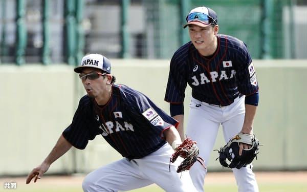 三塁の守備練習をする松田(手前)と坂本勇(28日、那覇市)=共同