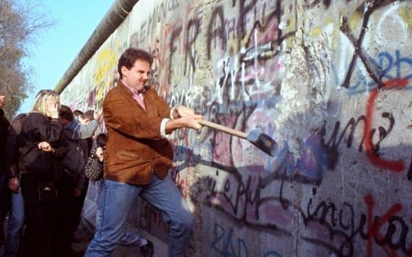 ベルリンの壁をハンマーでたたき壊す男性(1989年11月)=AP