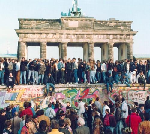1989年11月当時の様子。ブランデンブルク門前の壁によじ登り、東西ドイツの人たちが歓声を上げた(AP)