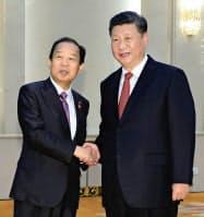 4月、会談を前に、中国の習近平国家主席(右)と握手する自民党の二階幹事長=北京の人民大会堂(共同)
