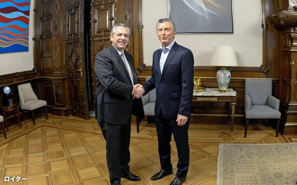 大統領府にフェルナンデス次期大統領(左)を迎え握手するマクリ大統領(28日、ブエノスアイレス)=ロイター