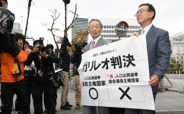 参院選「1票の格差」訴訟の判決後、大阪高裁前で垂れ幕を掲げる原告側の升永英俊弁護士(左)ら(29日午後、大阪市北区)