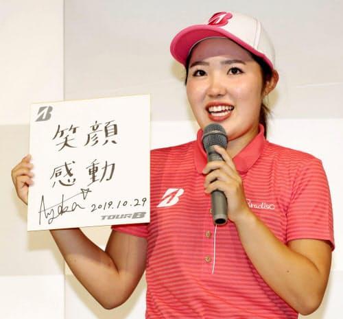 「笑顔 感動」と書かれた色紙を手に、記者会見する女子ゴルフの古江彩佳(29日午前、東京都内)=共同