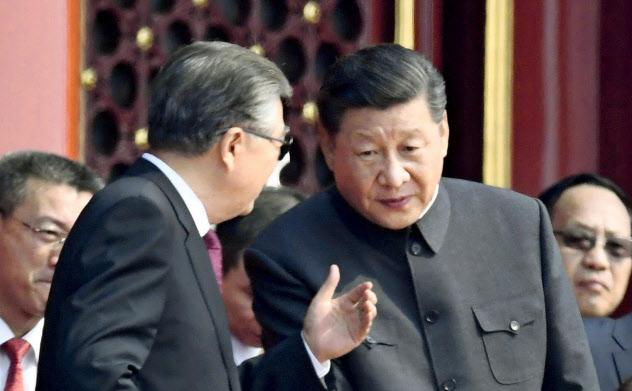 建国70年記念式典で胡錦濤前国家主席(左)と話す習近平国家主席(1日、北京の天安門)=共同