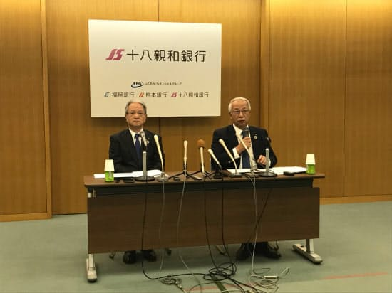 営業拠点の統合を発表する十八銀行の森拓二郎頭取(右)と親和銀行の吉沢俊介頭取(29日、長崎市)