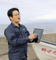 ナマコの密漁について話す地元漁協の中川貴世仁・総括課長。手元のタブレット端末に不審船の情報が入る(7日、青森県蓬田村)=共同