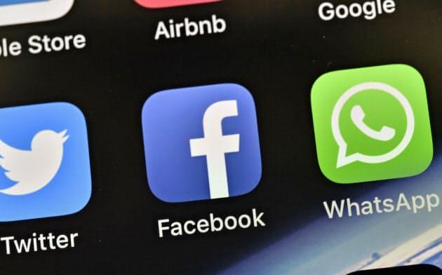 携帯電話の画面でフェイスブック(中)と並んだワッツアップのアイコン(右)=AP