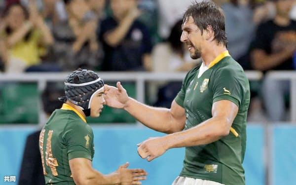 1次リーグのイタリア戦でトライを決め、203センチのエツベス(右)に祝福される南アフリカのコルビ。170センチとひときわ小柄だが、快足のトライゲッターだ=共同