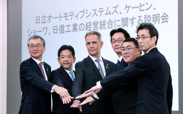 傘下の部品メーカーの統合を発表し握手する日立製作所の小島副社長(左端)ら(30日、東京都台東区)