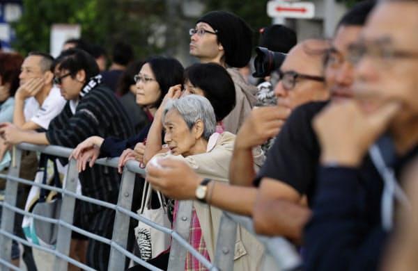 不安そうな表情で火災が発生した首里城を見つめる人たち(31日、那覇市)