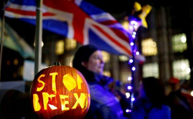 29日、ロンドンの国会議事堂前で「英国のEU離脱反対」と記したカボチャを掲げる人々=ロイター