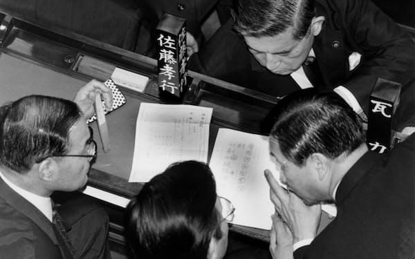 衆院本会議場で内閣不信任決議の票読みをする自民党議員=1993年6月18日午後7時すぎ、国会。