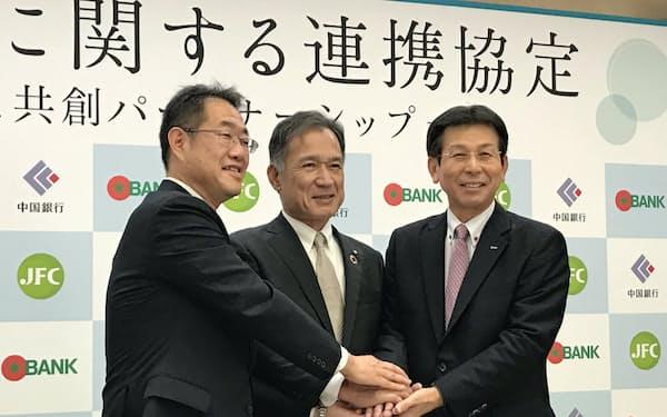 協定書締結後に握手する(左から)日本公庫の龍門支店長、中国銀の加藤頭取、トマト銀の高木社長(31日、岡山市)
