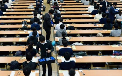 大学入試センター試験で、受験生にリスニング用の機器を配布する担当者(1月、東京都文京区の東京大学)