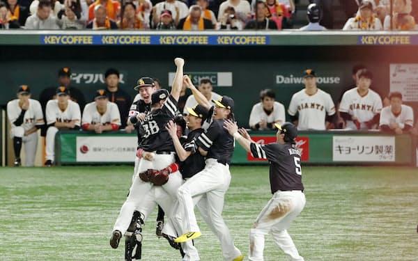 日本シリーズ3連覇を果たし、沈黙する巨人ベンチの前で喜ぶソフトバンクナイン=共同