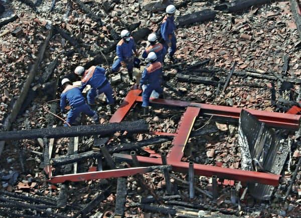 火災で焼失した首里城の正殿付近を調べる消防隊員ら(1日午後、那覇市)=共同通信社ヘリから