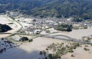 台風19号の影響で阿武隈川(手前)が氾濫し、浸水した宮城県丸森町の市街地(10月13日)=共同