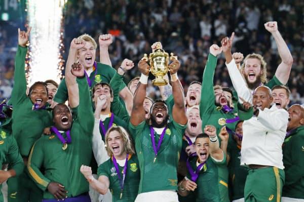優勝杯の「ウェブ・エリス・カップ」を手にする南アフリカのコリシ主将と喜ぶフィフティーン(2日、横浜市の横浜国際総合競技場)