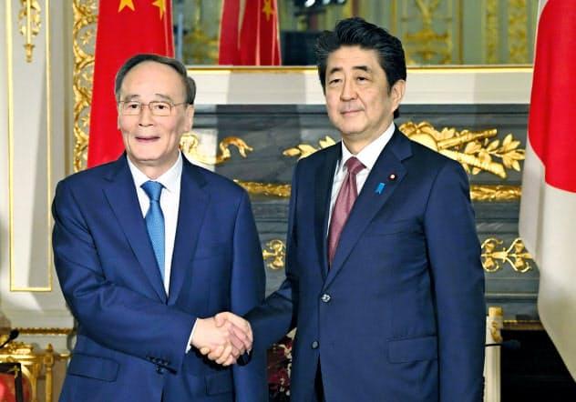 会談前に握手する安倍首相(右)と中国の王岐山国家副主席=10月23日、東京・元赤坂の迎賓館(代表撮影)