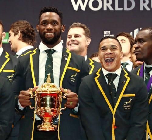 ワールドラグビーの年間表彰式を前に、記念撮影で笑顔を見せる南アフリカのコリシ主将(手前左)、コルビ(同右)ら。奥中央はエラスムス監督(3日夜、東京都内)=共同