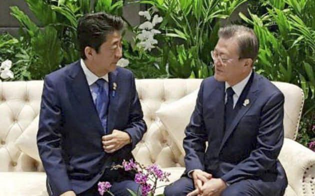 4日、バンコクで歓談する安倍首相(左)と韓国の文在寅大統領=聯合・共同