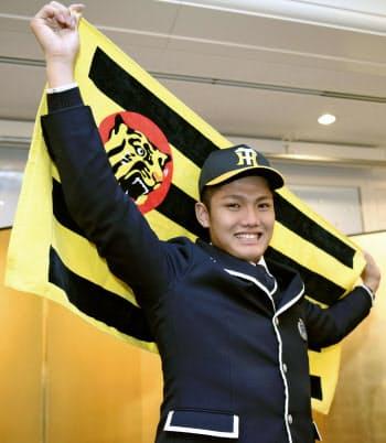 阪神への入団が決まり、笑顔でポーズをとるドラフト1位の西純矢投手(4日、岡山市)=共同