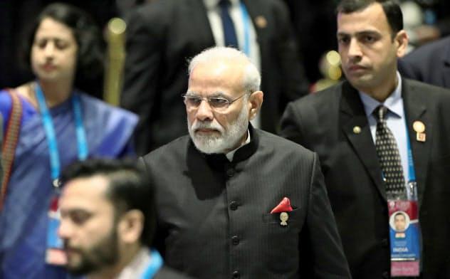 関税撤廃などで慎重な姿勢を崩さないインドのモディ首相(中)(4日、バンコク)=ロイター