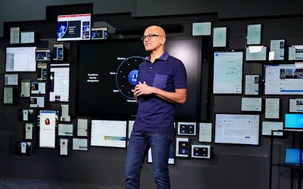マイクロソフトのナデラ氏は講演のさなか、多数のハードウエアを貼り付けた壁の前に移動して「端末の革新」について語った(4日、フロリダ州オーランド)