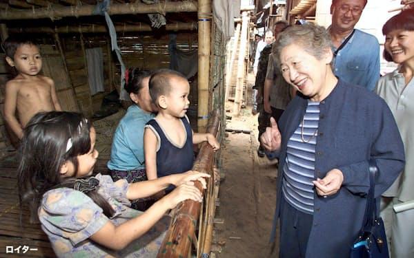 2000年10月、タイに逃れたミャンマーの難民家族と言葉を交わす緒方貞子氏=ロイター