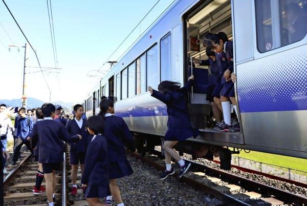 「津波防災の日」に合わせた防災訓練で、列車から避難する小学生ら(5日午前、和歌山県広川町)=共同