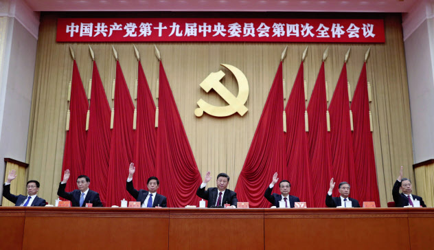 中国共産党の第19期中央委員会第4回全体会議で挙手する政治局常務委員。中央は習近平総書記(北京)=新華社・共同