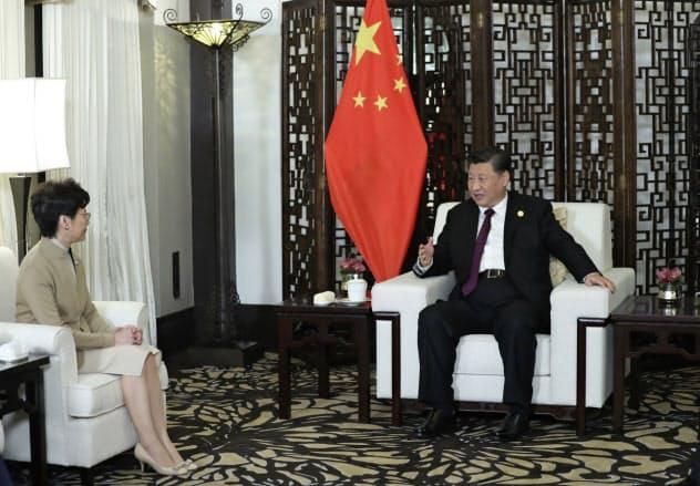 習近平国家主席(右)と会談する香港の林鄭月娥行政長官(4日、上海)=新華社・AP